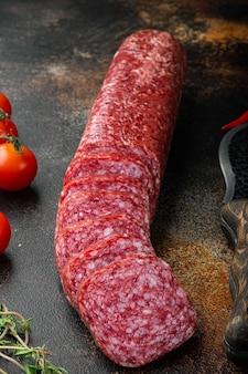 Geschnittenes salami-set, auf altem dunklem rustikalem tischhintergrund