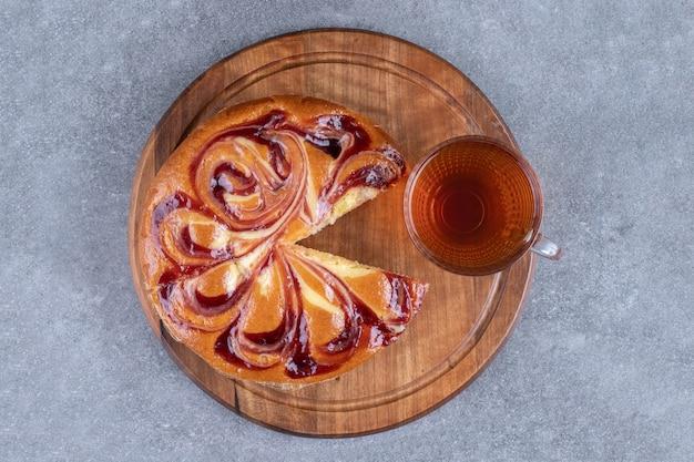 Geschnittenes süßes brot und eine tasse tee auf einem brett