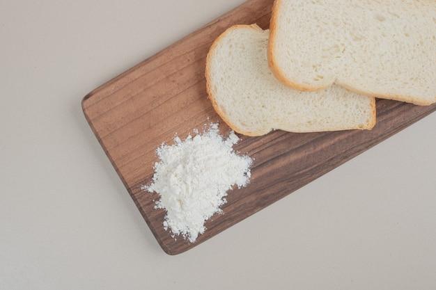 Geschnittenes weißbrot mit mehl auf holzbrett