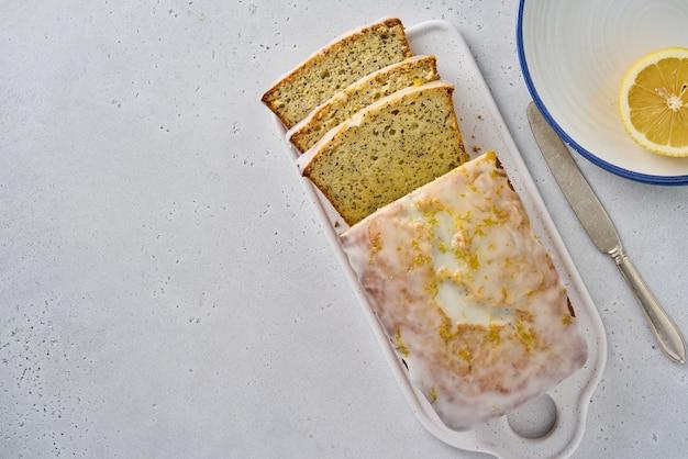Geschnittenes zitronenbrot mit mohn, zitrusschale und weißem zuckerguss, leckeres dessert
