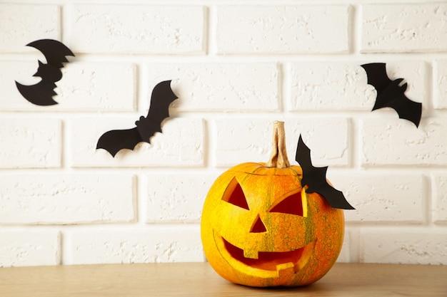 Geschnitzter leuchtender kürbis und schwarze fledermäuse auf hellem hintergrund. halloween-feier. draufsicht