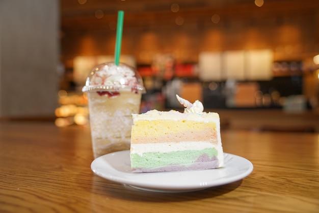 Geschobener regenbogenkuchen mit einhornhorn oben neben kaffeefrappe verzieren. der kuchen liegt in einer weißen scheibe auf dem holztisch