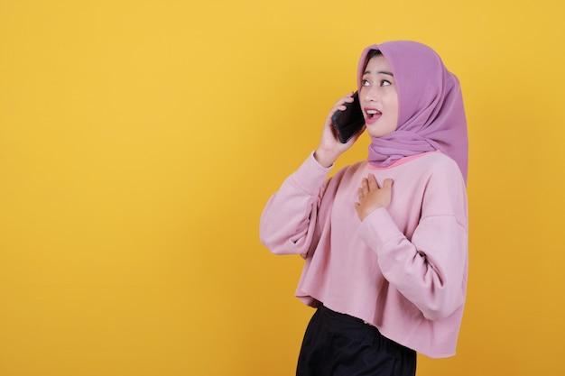 Geschockt von attraktiver schöner frau hält modernes handy in der hand und telefoniert mit jemandem