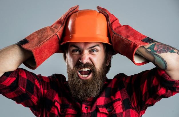 Geschockter assistent. technisches konzept. werkzeugwerkstatt reparieren. bärtiger mann arbeiter im helm. reifer kerl baumeister mit bart und schnurrbart. männlicher vorarbeiter in uniform. hübscher hipster auf der baustelle.