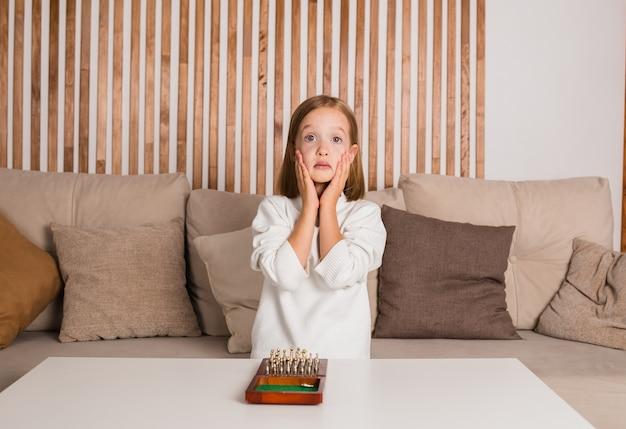 Geschockter kleiner schachspieler im weißen pullover sitzt auf dem sofa und spielt schach