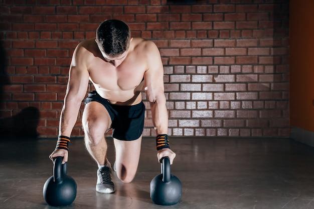 Geschossen vom gesunden muskulösen jungen mann, der gewichtsübung mit dummköpfen tut