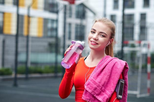 Geschossen vom schönen weiblichen läufer, der draußen steht, halten wasserflasche. eignungsfrau, die eine pause nach laufendem training macht