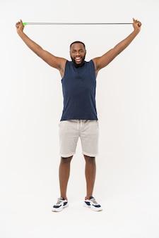 Geschossen vom springseil des männlichen mannes, muskulöser junger mann, der mit springendem seil auf grau trainiert