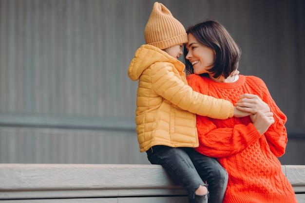 Geschossen von der liebevollen jungen frau in der warmen roten sweaterromotion