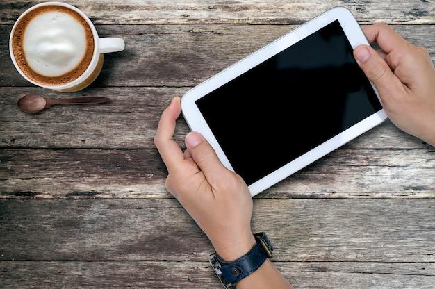 Geschossen von der mannhand, die weiße tablette mit schwarzem schirm auf altem holztisch, kopienraum für text hält.