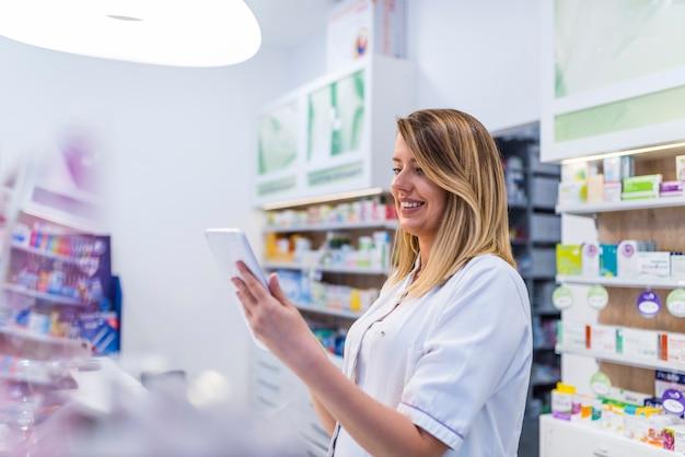 Geschossen von einem apotheker, der unter verwendung einer digitalen tablette betrachtet die regale am drugstor arbeitet