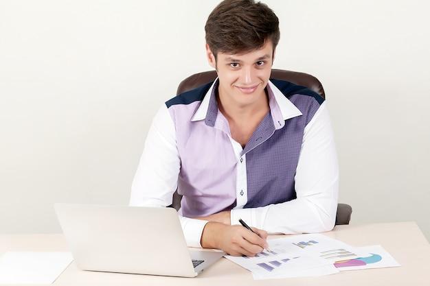 Geschossen von einem hübschen kreativen direktorengeschäftsmann, der im büro beim sitzen am schreibtisch mit laptop arbeitet.