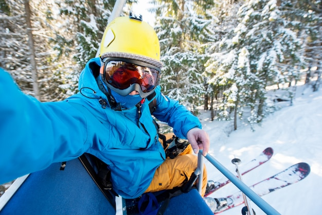 Geschossen von einem völlig ausgerüsteten skifahrer, der himmel, gelben sturzhelm und die skimaske trägt, die ein selfie beim reiten des skilifts in den bergen nehmen