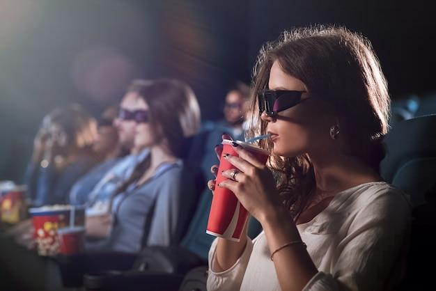 Geschossen von einer schönen frau in den gläsern 3d, die an ihrem getränk beim aufpassen eines films nippen