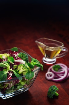 Geschredderte zutaten für bio-salat mit brokkoli und zwiebeln, olivenöl in glasschüssel