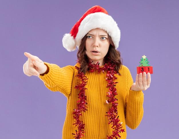 Geschütteltes junges slawisches mädchen mit weihnachtsmütze und mit girlande um den hals hält weihnachtsbaumverzierung, die auf seite lokalisiert auf lila hintergrund mit kopienraum schaut und zeigt