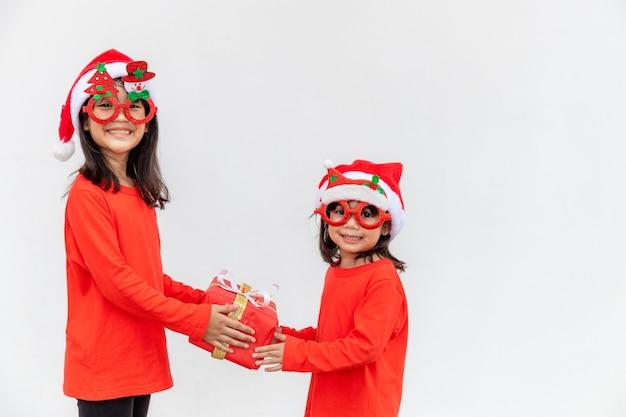Geschwister asiatische mädchen in roter weihnachtsmütze mit geschenkboxen auf weißem hintergrund.