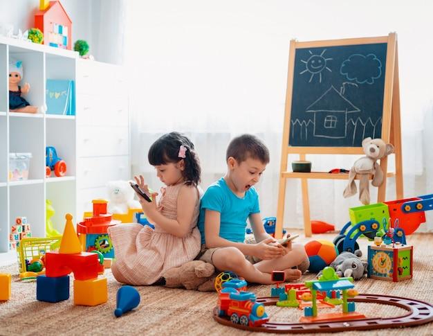 Geschwister auf dem boden spielen mit smartphones