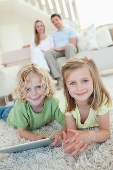 Geschwister auf dem teppich mit tablet und eltern hinter ihnen