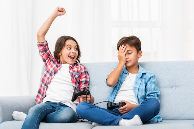 Geschwister auf der couch, die mit steuerknüppel spielt