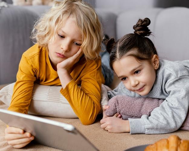 Geschwister auf der couch mit tablette