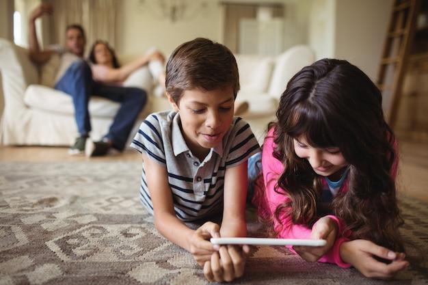 Geschwister auf teppich liegend und mit digitalem tablet im wohnzimmer