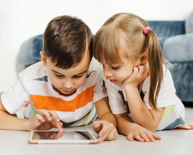 Geschwister der vorderansicht mit einem digitalen tablet