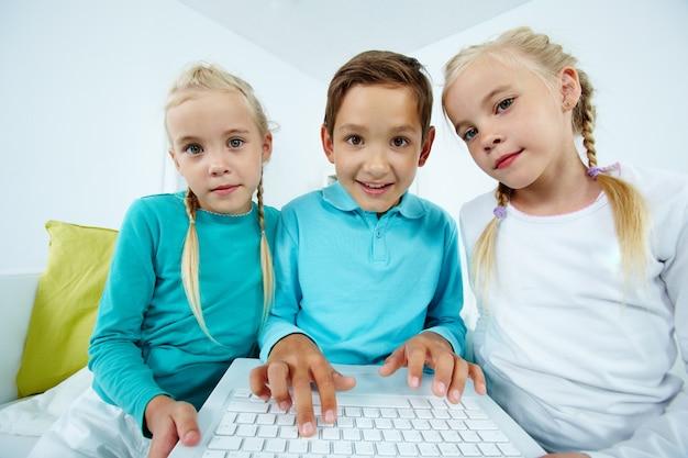 Geschwister, die auf dem sofa sitzt mit laptop