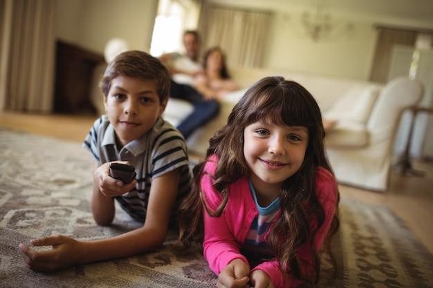 Geschwister, die auf teppich liegen und im wohnzimmer fernsehen