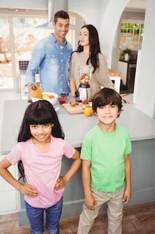 Geschwister, die bei tisch mit den eltern zubereiten fruchtsaft stehen