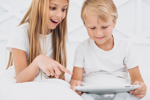 Geschwister, die etwas lustig auf einer tablette aufpassen