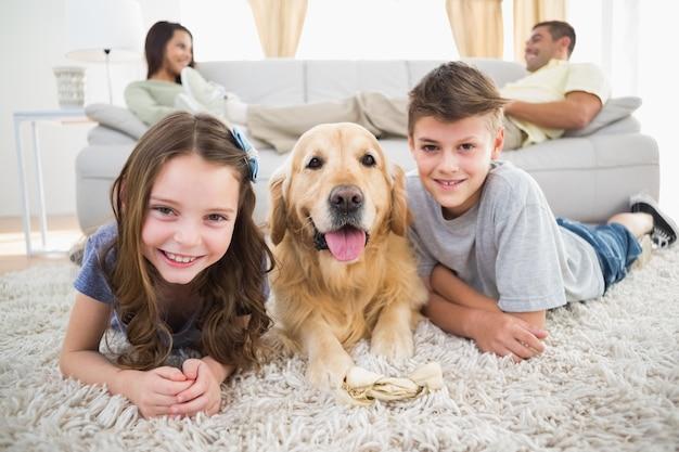 Geschwister, die mit hund während eltern entspannen auf sofa liegen