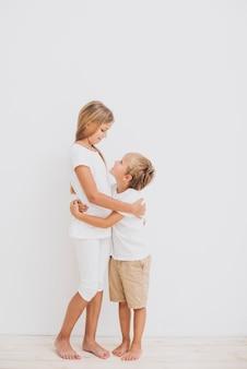 Geschwister, die mit weißem hintergrund umarmen