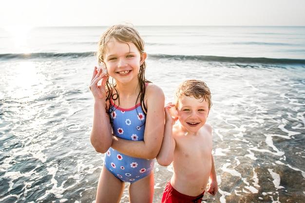 Geschwister, die spaß am strand haben