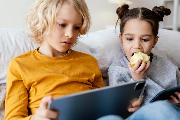 Geschwister im bett spielen auf handy und tablet