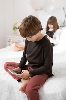 Geschwister im schlafzimmer mit telefon
