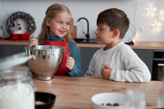 Geschwister in der küche während der weihnachtszeit