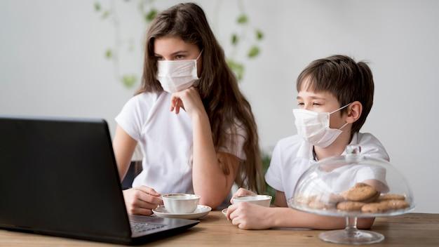 Geschwister mit maske, die auf laptop schaut