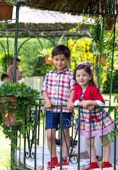 Geschwister mit passender kleidung und lächeln in die kamera umgeben von natur