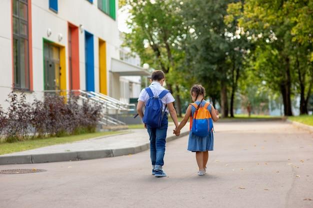 Geschwister mit rucksäcken zu fuß zur schule