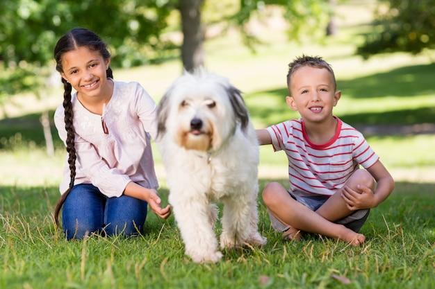 Geschwister sitzen mit ihrem hund im park