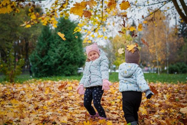 Geschwister spielen mit blättern im herbstpark. glückliches baby und junge