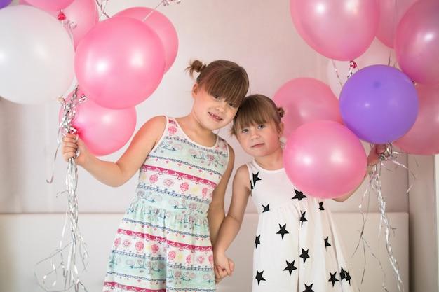 Geschwister spielen mit luftballons, konzept kindheit