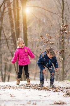 Geschwister springen zusammen in einem wald mit trockenen blättern im winter