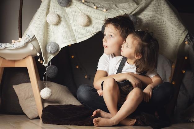 Geschwister umarmen sich in einer hütte aus stühlen und decken. bruder und schwester spielen zu hause