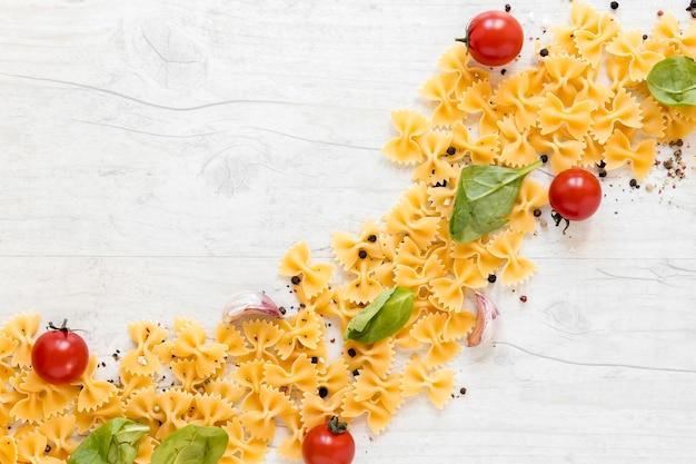 Geschwungene form mit farfalle-nudeln und tomaten; knoblauchzehe; basilikumblatt auf hölzernem hintergrund