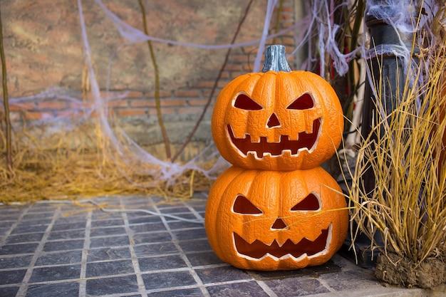 Gesehnte kürbiskopf-klinkenlaterne auf reisstroh im halloween-thema gelegt.