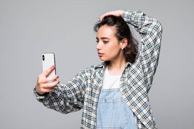 Gesellige schöne frau mit asiatischem aussehen, das selfie nimmt oder auf videoanruf unter verwendung des isolierten mobiltelefons spricht
