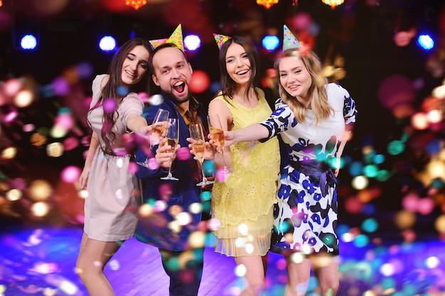 Gesellschaft fröhlicher freunde in festlichen hüten, um das ereignis zu feiern