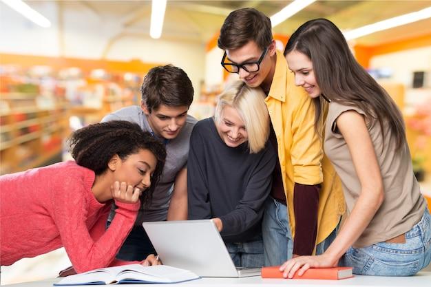 Gesellschaft junger glücklicher studenten mit laptop in der bibliothek